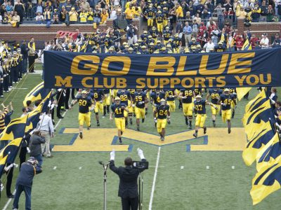 Michigan football players running out on the field.